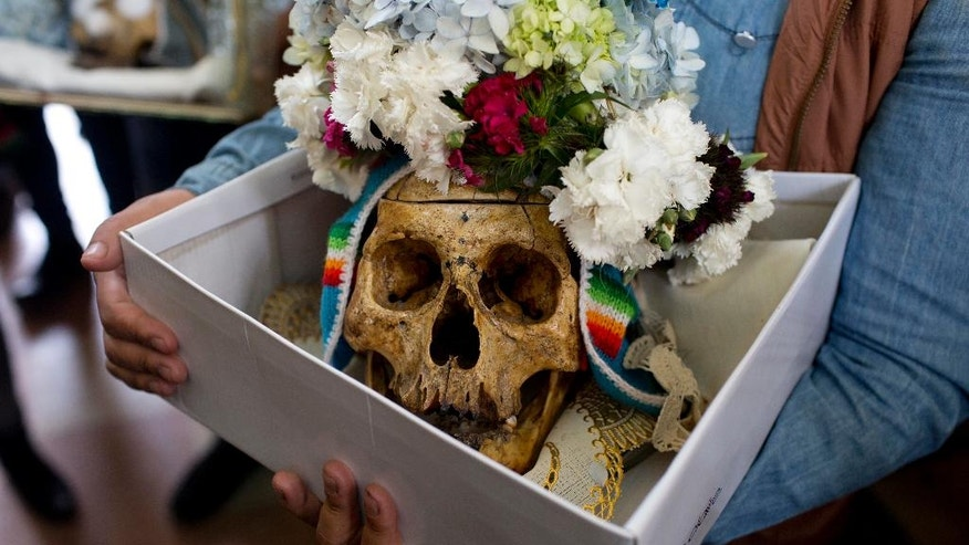 """A woman holds a box with a decorated human skull or """"natitas"""" as she waits to be greeted by the priest inside the Cementerio General chapel, during the Natitas Festival celebrations, in La Paz, Bolivia, Tuesday, Nov. 8, 2016. The """"natitas"""" are cared for and decorated by faithful who use them as amulets believing they serve as protection, the tradition marks the end of the Catholic All Saints holiday, but is not recognized by the Catholic church. (AP Photo/Juan Karita)"""