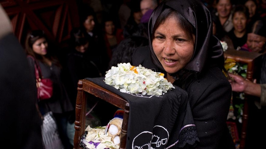 """A woman carries a decorated human skull or """"natitas,"""" after a blessing by the priest inside the Cementerio General chapel, during the Natitas Festival celebrations, in La Paz, Bolivia, Tuesday, Nov. 8, 2016. The """"natitas"""" are cared for and decorated by faithful who use them as amulets believing they serve as protection, the tradition marks the end of the Catholic All Saints holiday, but is not recognized by the Catholic church. (AP Photo/Juan Karita)"""