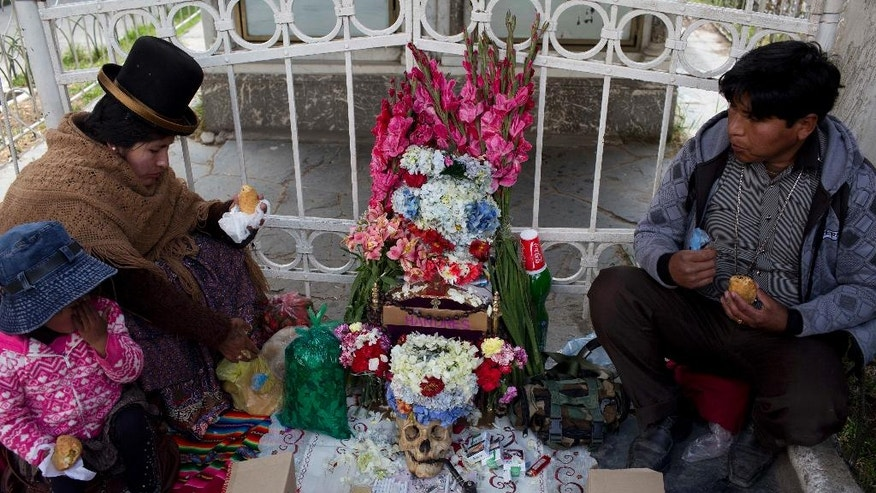 """A couple sits with a decorated human skull or """"natitas,"""" during the Natitas Festival celebrations, in La Paz, Bolivia, Tuesday, Nov. 8, 2016. The """"natitas"""" are cared for and decorated by faithful who use them as amulets believing they serve as protection, the tradition marks the end of the Catholic All Saints holiday, but is not recognized by the Catholic church. (AP Photo/Juan Karita)"""