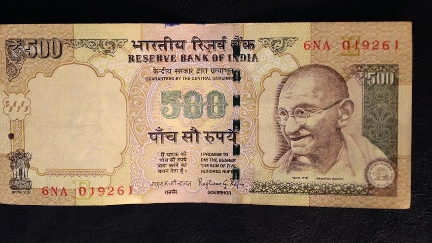 This photo illustration shows a 500 rupee Indian currency note which is being withdrawn from midnight Tuesday, in New Delhi, India, Tuesday, Nov. 8, 2016. India's highest-denomination currency notes are being withdrawn immediately from circulation, the country's prime minister said Tuesday night, a surprise announcement designed to fight corruption and target people who have stashed away immense amounts of cash. As of midnight Tuesday, 500- and 1,000-rupee notes, worth about $7.50 and $15, will have no cash value, Prime Minister Narendra Modi said in a televised address. (AP Photo/Manish Swarup)