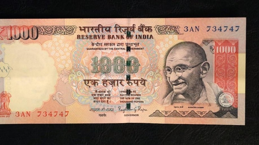This photo illustration shows a 1000 rupee Indian currency note which is being withdrawn from midnight Tuesday, in New Delhi, India, Tuesday, Nov. 8, 2016. India's highest-denomination currency notes are being withdrawn immediately from circulation, the country's prime minister said Tuesday night, a surprise announcement designed to fight corruption and target people who have stashed away immense amounts of cash. As of midnight Tuesday, 500- and 1,000-rupee notes, worth about $7.50 and $15, will have no cash value, Prime Minister Narendra Modi said in a televised address. (AP Photo/Manish Swarup)