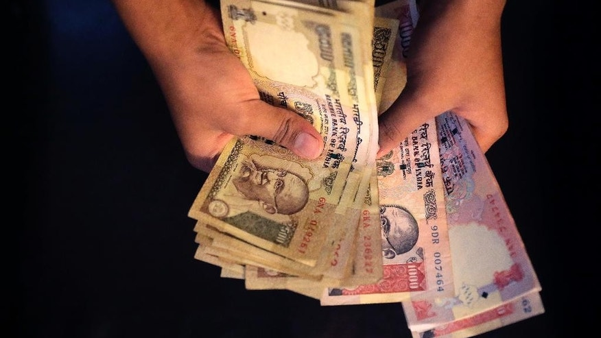 An Indian counts currency notes of 1000 and 500 denomination in New Delhi, India, Tuesday, Nov. 8, 2016. India's highest-denomination currency notes are being withdrawn immediately from circulation, the country's prime minister said Tuesday night, a surprise announcement designed to fight corruption and target people who have stashed away immense amounts of cash. As of midnight Tuesday, 500- and 1,000-rupee notes, worth about $7.50 and $15, will have no cash value, Prime Minister Narendra Modi said in a televised address. (AP Photo/Manish Swarup)