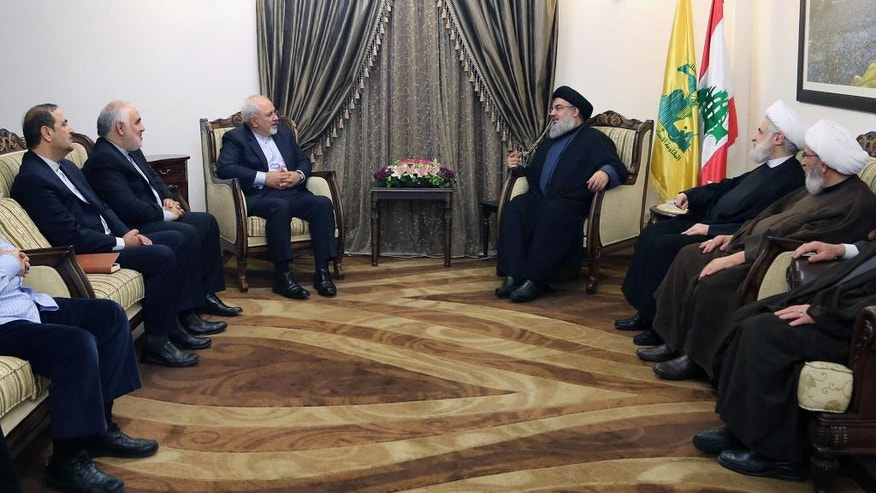In this photo released by the Hezbollah media department, Hezbollah leader Sayyed Hassan Nasrallah, center right, meets with Iranian Foreign Minister Mohammad Javad Zarif, center left, in Beirut, Lebanon, Tuesday, Nov. 8, 2016. Zarif called for a political solution to the conflicts in Yemen and Syria, saying that the continuation of violence will only lead to more bloodshed and no one will win the war. Iran is a strong backer of Yemen's Shiite rebels known as Houthis and also Syrian President Bashar Assad. Saudi Arabia -- Iran's main regional rival -- backs the Yemeni government fighting the Houthis and insurgents trying to remove Assad from power. (AP Photo/Hezbollah Media Department)