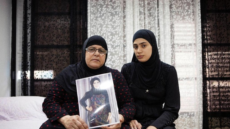 In this photo taken Thursday, Nov. 3, 2016. Israeli Arab Majeda Abu Sharkh left, holds a picture of Duaa Abu Sharkh that was killed in Lod as she poses for a photograph with her niece Alaa Khalili, in Lod, central Israel. After years of abuse and death threats, Duaa Abu-Sharkh had finally divorced her husband, agreeing even to give up custody of her four young children to escape his violent grip. Then, one night in late September, as she was dropping off her kids after a rare visitation, a masked gunman dragged her from her car in the center of this crime-ridden city and shot her in the head before their eyes.  (AP Photo/Dan Balilty)
