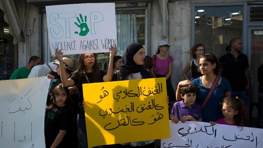 """In this photo taken Friday, Oct. 28, 2016, Israeli Arab women hold signs during a demonstration in Jaffa, Israel. Arabic sign reads:""""Verbal violence, is like physical violence, is like murder.""""  A string of murders of Israeli-Arab women by suspected relatives has sparked soul searching in the community and unprecedented demonstrations against its treatment of women. After years of silence, Arab citizens are now calling for more police and social services in their long-neglected neighborhoods. (AP Photo/Sebastian Scheiner)"""