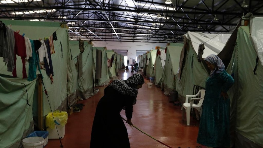 A woman mops the floor outside her tent inside the building of the Kalochori refugee camp, set up in a disused supermarket, on the outskirts of the northern Greek city of Thessaloniki, Tuesday, Nov. 8, 2016. More than 60,000 refugees are stranded in Greece, unable to continue their journeys northward to more prosperous European Union countries after Balkan countries shut down their land borders to refugees earlier this year. (AP Photo/Thanassis Stavrakis)