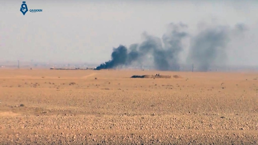 This frame grab from video provided by Qasioun a Syrian opposition media outlet, shows smoke rising as a result of clashes between U.S.-backed forces and the Islamic State group, near Ein Issa, north of Raqqa, Syria. Backed by U.S. airstrikes, Kurdish-led Syrian fighters clashed on Monday with Islamic State militants north of the city of Raqqa in Syria as they pushed ahead in their offensive aiming to liberate the city that has been the de facto capital of the extremist group since 2014. (Qasioun a Syrian Opposition Media Outlet, via AP)