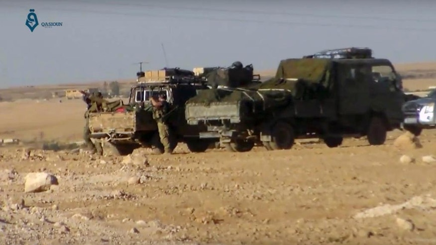 This frame grab from a video provided by Qasioun a Syrian opposition media outlet, shows U.S.-backed Syrian Democratic Forces fighters stationed near Ein Issa, north of Raqqa, Syria. Backed by U.S. airstrikes, Kurdish-led Syrian fighters clashed on Monday with Islamic State militants north of the city of Raqqa in Syria as they pushed ahead in their offensive aiming to liberate the city that has been the de facto capital of the extremist group since 2014. (Qasioun a Syrian Opposition Media Outlet, via AP)
