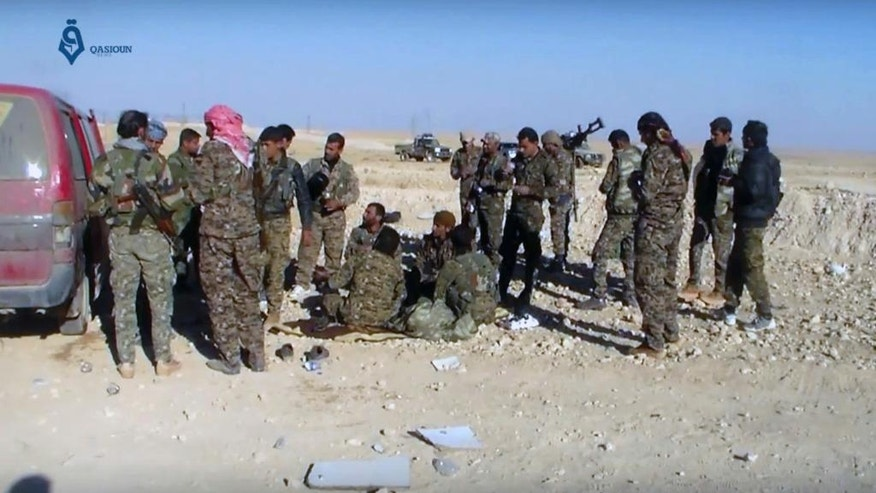 This frame grab from video provided by Qasioun a Syrian opposition media outlet, shows U.S.-backed fighters taking a rest during fighting with the Islamic State group near Ein Issa, north of Raqqa, Syria. Backed by U.S. airstrikes, Kurdish-led Syrian fighters clashed on Monday with Islamic State militants north of the city of Raqqa in Syria as they pushed ahead in their offensive aiming to liberate the city that has been the de facto capital of the extremist group since 2014. (Qasioun a Syrian Opposition Media Outlet, via AP)