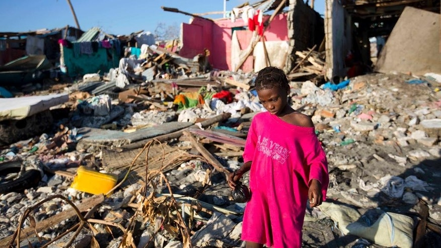 "FILE - This is a Wednesday, Oct. 12, 2016. file photo of a girl as she walks through debris where homes once stood after Hurricane Matthew hit Jeremie, Haiti. Hot and wild and with an ""increasingly visible human footprint"" _ that's how the U.N. weather agency summed up the global climate in the past five years. In a report released Tuesday Nov. 8, 2016 at international climate talks in Morocco, the World Meteorological Organization said 2011-2015 was the hottest five-year period on record. (AP Photo/Dieu Nalio Chery, File)"