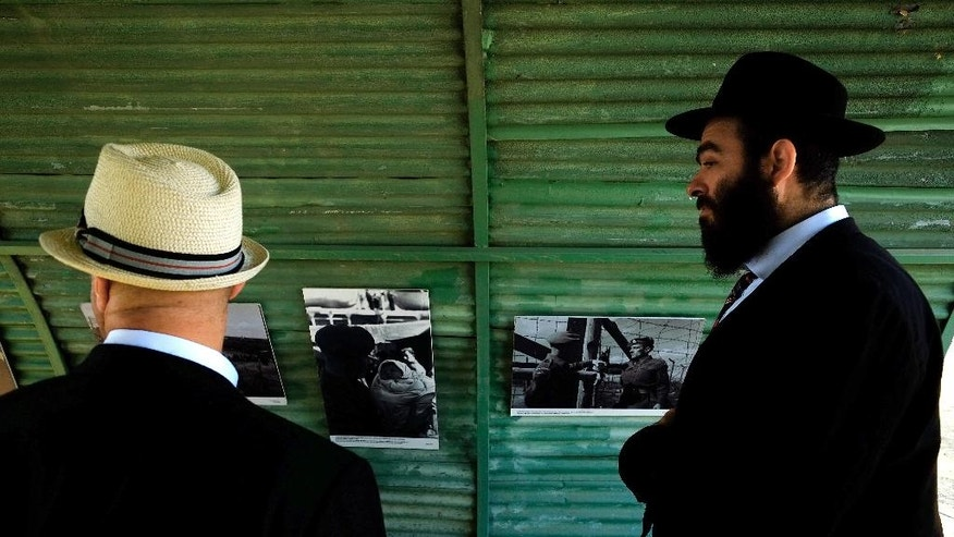 Jewish men look at the vintage photos of the British camp on a recreation of a semi-circular, corrugated iron hut that housed detainees, at the Cypriot military camp in capital Nicosia, on Wednesday, Nov. 9, 2016. Dozens of people born to Jewish refugees interned in Cyprus after World War II have marked the 70th anniversary of the start of such detentions at a ceremony on the east Mediterranean island. A memorial commemorating the event was unveiled at a Cypriot army camp that formerly housed a British military hospital where hundreds of Jewish infants were born. (AP Photo/Petros Karadjias)