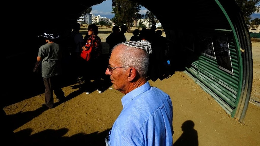A Jewish man stands in front of a recreation of a semi-circular, corrugated iron hut that housed detainees, at the Cypriot military camp in capital Nicosia, on Wednesday, Nov. 9, 2016. Dozens of people born to Jewish refugees interned in Cyprus after World War II have marked the 70th anniversary of the start of such detentions at a ceremony on the east Mediterranean island. A memorial commemorating the event was unveiled at a Cypriot army camp that formerly housed a British military hospital where hundreds of Jewish infants were born. (AP Photo/Petros Karadjias)