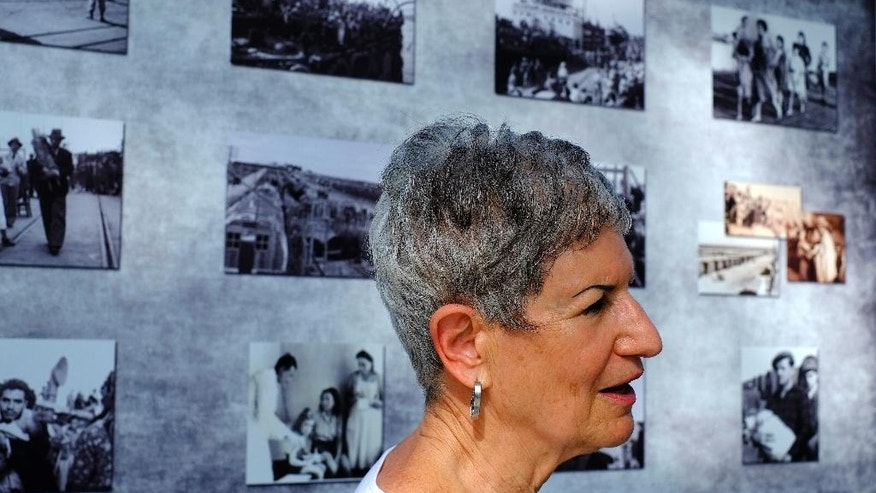 Nechema Friedman, 69, who was born at the hospital stands next to photos of that period in the British military camp, at the Cypriot military camp in capital Nicosia, on Wednesday, Nov. 9, 2016. Dozens of people born to Jewish refugees interned in Cyprus after World War II have marked the 70th anniversary of the start of such detentions at a ceremony on the east Mediterranean island. A memorial commemorating the event was unveiled at a Cypriot army camp that formerly housed a British military hospital where hundreds of Jewish infants were born. (AP Photo/Petros Karadjias)