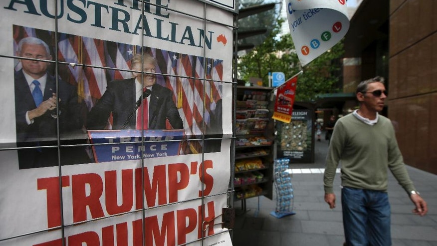 """A man walks past a newspaper placard, showing President-elect Donald Trump, in Sydney, Thursday, Nov. 10, 2016, following the U.S. presidential election. Australian Prime Minister Malcolm Turnbull says his country will work """"as closely as ever"""" with the United States under Donald Trump's new administration. (AP Photo/Rick Rycroft)"""