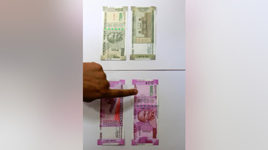 Specimens of the new Indian Rupees 500, top, and 1,000 currency are displayed at the Reserve Bank of India headquarters in Mumbai, India, Wednesday, Nov. 9, 2016. Indians awakened to confusion Wednesday as banks and ATMs remained closed after the government withdrew the highest-denomination currency notes overnight to halt money laundering in a country where many in the poor and middle-class still rely mainly on cash. The government will issue new banknotes of 500 and 2,000 rupee denominations soon, Finance Minister Arun Jaitley said, adding that the new currency should be available in banks within three or four weeks. (AP Photo/Rajanish Kakade)