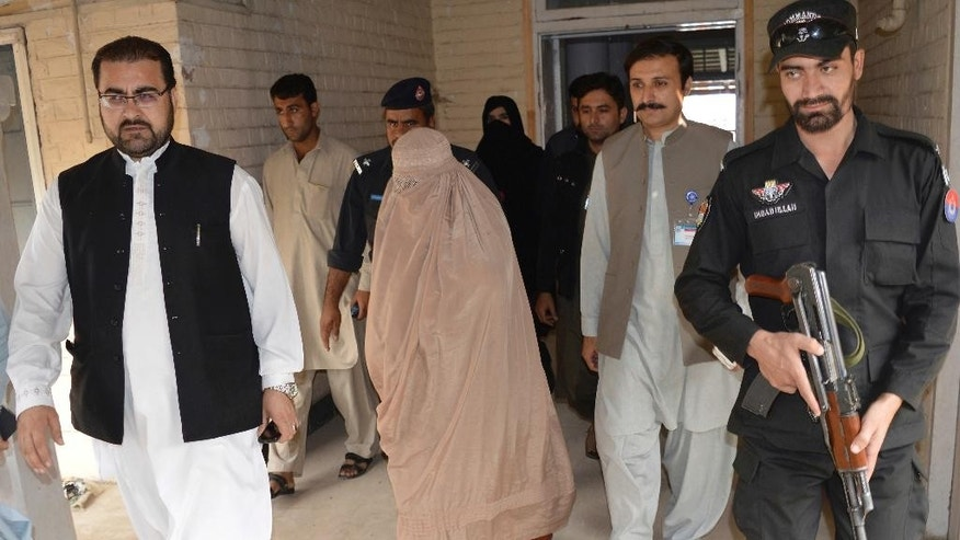 "FILE - In this Nov. 4, 2016 file photo, Pakistani officials escort famed Afghan woman Sharbat Gulla in a burqa or veil outside a court in Peshawar, Pakistan. A Pakistani government official says on Wednesday, Nov. 9, National Geographic's famed green-eyed ""Afghan Girl"" has been deported to Afghanistan. Fayaz Khan says Pakistani officials handed over Gulla and her four children to Afghan authorities early Wednesday at Torkham border, 60 kilometers (37 miles) northwest of Peshawar city. (AP Photo/Mohammad Sajjad, File)"
