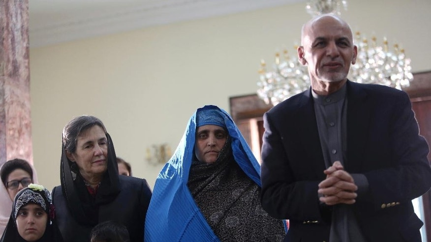 "Afghan President Ashraf Ghani, right, meets with National Geographic's famed green-eyed ""Afghan Girl"" Sharbat Gulla at the Presidential palace in Kabul, Afghanistan, Nov. 9, 2016. Afghanistan's president on Wednesday welcomed home Gulla who was deported from Pakistan after a court had convicted her on charges of carrying a forged Pakistani ID card and staying in the country illegally. (AP Photo/Rahmat Gul)"