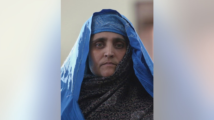 Afghan famed woman Sharbat Gulla meet with Afghan President Ashraf Ghani, at the Presidential palace in Kabul, Afghanistan, Nov. 9, 2016, Afghanistan's president on Wednesday welcomed home the famed green-eyed girl who was deported from Pakistan after a court had convicted her on charges of carrying a forged Pakistani ID card and staying in the country illegally. (AP Photo/Rahmat Gul)