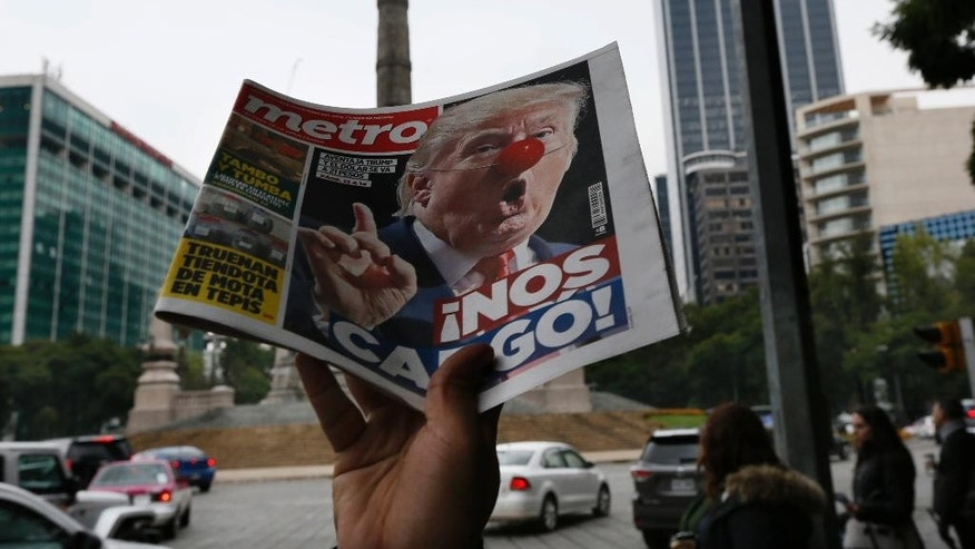 "A street vendor hawks a newspaper emblazoned with an image of Donald Trump with a clown's nose, and a headline that reads in Spanish: ""We're screwed!,"" in front of the Angel of Independence monument, in Mexico City, Wednesday, Nov. 9, 2016. President-elect Trump's triumph over Hillary Clinton ends eight years of Democratic dominance of the White House. Trump has pledged to usher in sweeping changes to U.S. foreign policy, including building a wall along the U.S.-Mexico border. (AP Photo/Marco Ugarte)"