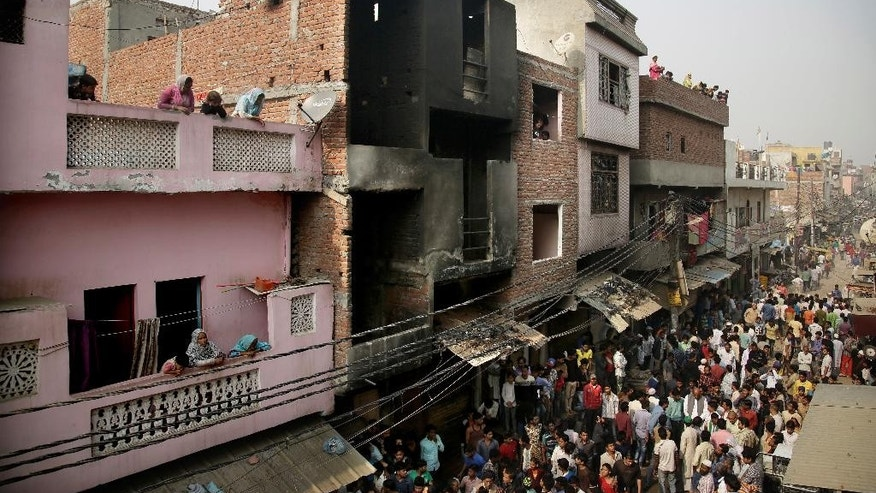 Locals crowd outside a residential building used as a garment factory, which was gutted in a fire in the outskirts of New Delhi, India, Friday, Nov. 11, 2016. The fire, that broke out the garment factory basement, trapped and killed more than a dozen workers as they slept in the building. (AP Photo/Altaf Qadri)
