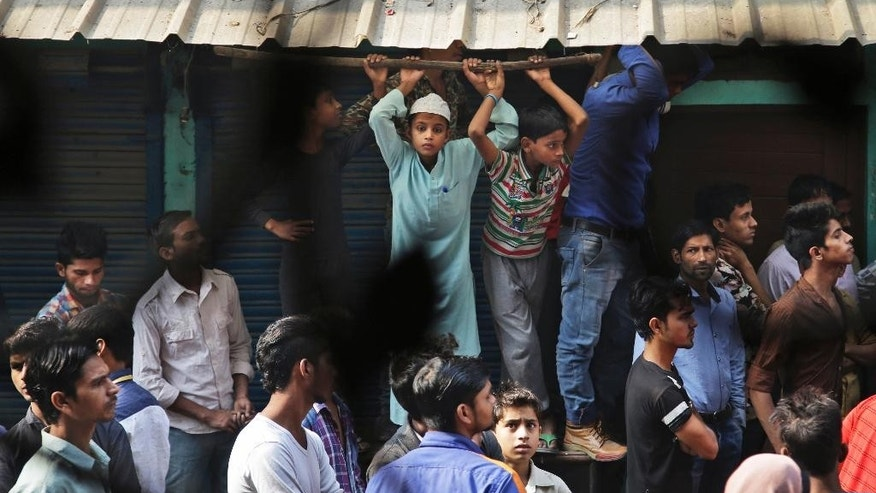 Locals crowd outside a residential building used as a garment factory, which was gutted in a fire in the outskirts of New Delhi, India, Friday, Nov. 11, 2016. The fire, that broke out at the garment factory basement, trapped and killed more than a dozen workers as they slept in the building. (AP Photo/Altaf Qadri)