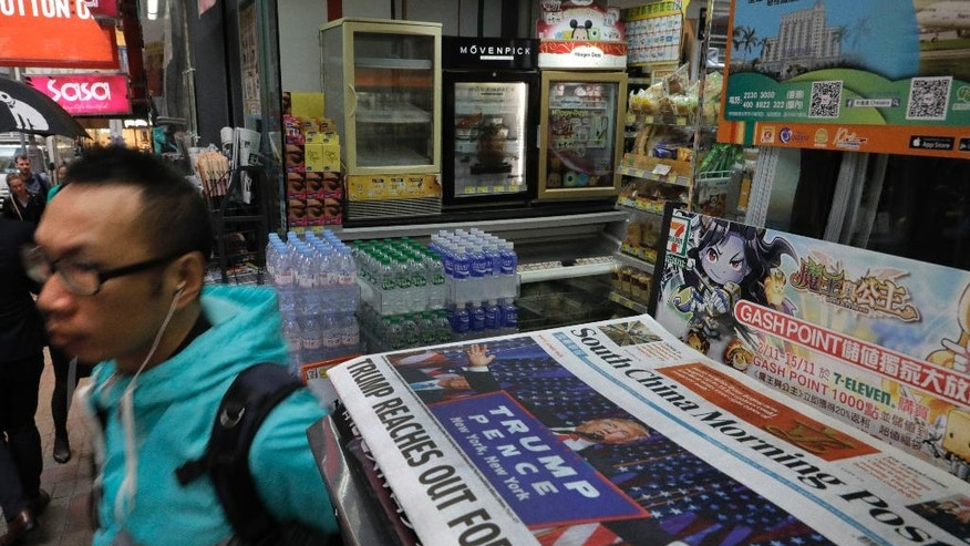 A man walks past a local newspaper reporting on the election victory of US President-elect Donald Trump in Hong Kong, Thursday, Nov. 10, 2016. (AP Photo/Vincent Yu)