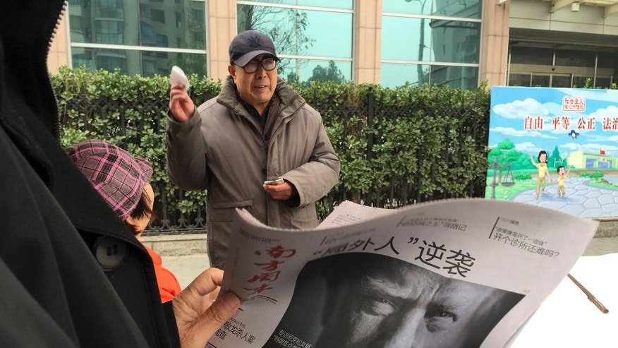 """A Chinese man holds up a Chinese newspaper with the front page photo of U.S. President-elect Donald Trump and the headline """"Outsider counter attack"""" at a newsstand in Beijing, China, Thursday, Nov. 10, 2016. (AP Photo/Ng Han Guan)"""