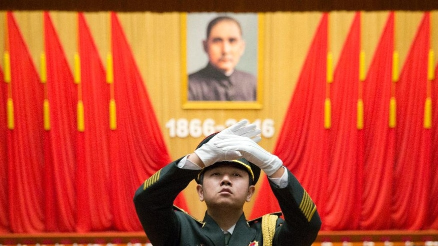 A band conductor leads a military band as participants leave near a commemorative meeting held to mark the 150th anniversary of the birth of Sun Yat-sen, founding father of the Republic of China and founder of the Chinese National Party (KMT) at the Great Hall of the People in Beijing, China, Friday, Nov. 11, 2016. Portrait in the background is of Sun.(AP Photo/Ng Han Guan)