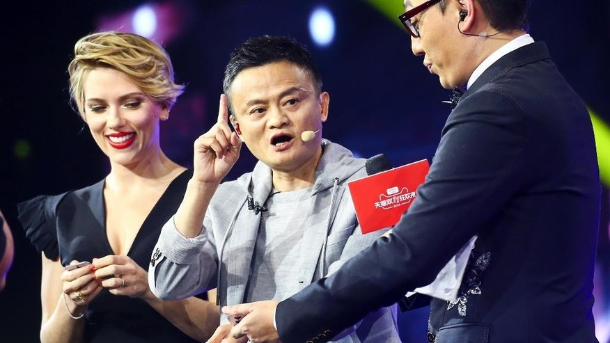 "In this Thursday, Nov. 10, 2016 photo, Hollywood actress Scarlett Johansson, left, and Alibaba Group Chairman Jack Ma, center, attend an evening gala on the eve of the Singles Day online shopping festival in Shenzhen in southern China's Guangdong province. China's online shoppers are engaging in a rare bright spot for its cooling economy — a quirky holiday dubbed ""Singles Day"" that has grown into the world's busiest day for e-commerce. The country's biggest e-commerce brand, Alibaba Group, said Friday sales by the thousands of retailers on its platforms passed 62.6 billion yuan ($9 billion) in the first 10 hours of the day. (Chinatopix Via AP)"