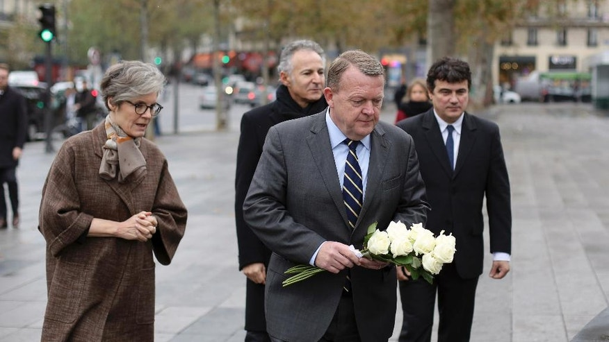 Danish ambassador to France, Kirsten Malling Biering, left, Danish Prime Minister Lars Lokke Rasmussen, center, and French columnist for Charlie Hebdo newspaper Patrick Pelloux, right, pay their respects to the victims of the 2015 Paris attacks, in Paris, Thursday, Nov. 10, 2016. (AP Photo/Thibault Camus)