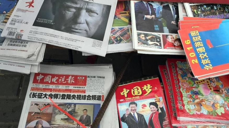 "A front page of a Chinese newspaper with a photo of U.S. President-elect Donald Trump and the headline ""Outsider counter attack"" is displayed at a newsstand in Beijing, China, Thursday, Nov. 10, 2016. Trump is a mixed blessing for Chinese leaders. His threats to tear up trade deals and hike tariffs on Chinese goods could chill thriving commercial ties when Beijing is struggling to shore up economic growth. At the same time, Trump's suggestion he might reduce Washington's global strategic presence to focus on domestic issues would be a gift to Chinese leaders. They could expand their political and military profile in East Asia with less risk of conflict. (AP Photo/Ng Han Guan)"