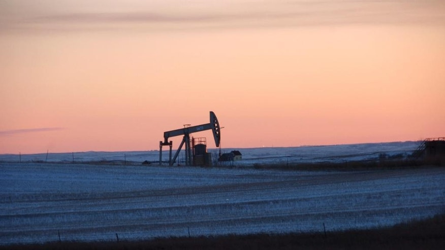 FILE - This Feb. 25, 2015, file photo, shows a pump jack for pulling oil from the ground, near New Town, N.D. On Tuesday, Nov. 8, 2016, the Energy Department said it is raising its forecast of U.S. production for both 2016 and 2017, as drillers respond to higher crude prices. Still, output won't match 2015, which was the biggest year for U.S. production in 35 years. (AP Photo/Matthew Brown, File)