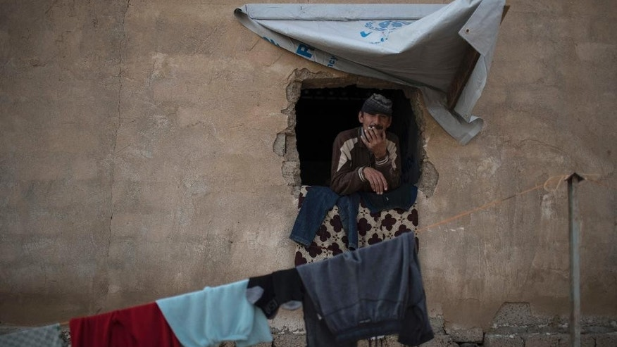 An Iraqi who was displaced by fighting in Mosul smokes in his window, at a camp for internally displaced people in Hassan Sham, east of Mosul, Iraq, Wednesday, Nov. 9, 2016. The United Nations says over 34,000 people have been displaced from Mosul, with about three quarters settled in camps and the rest in host communities. (AP Photo/Felipe Dana)