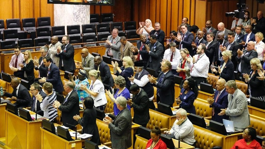 South African DA, Democratic Alliance party leader, Mmusi Maimane, far left, is applauded by his party members after he spoke and called for a motion to remove South African President Jacob Zuma as President at Parliament in Cape Town, South Africa, Thursday, Nov. 10, 2016. South Africa's parliament is debating a motion to remove President Jacob Zuma because of a series of scandals, including possible government corruption linked to the president and some associates. (AP Photo/Schalk van Zuydam)