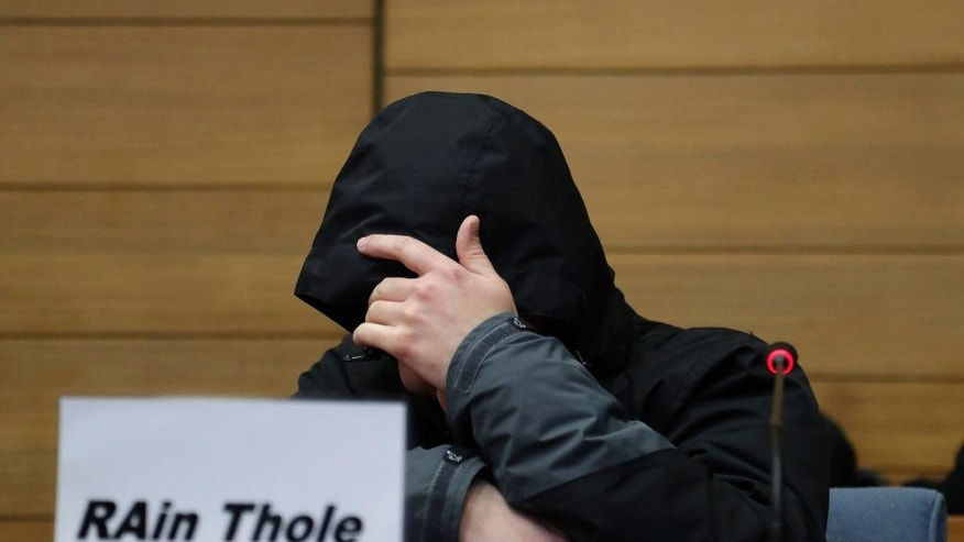 Defendant Michael P. covers his face as he arrives in a courtroom in Traunstein, southern Germany, Thursday, Nov. 10, 2016. The rail dispatcher is accused of negligent homicide in 12 cases as prosecutors claim he was playing an online game on his cellphone shortly before two trains he was in charge of collided head-on on a single-track line near Bad Aibling. (AP Photo/Matthias Schrader)
