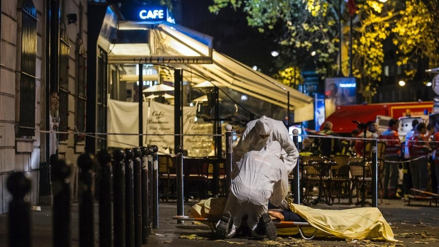 FILE - This is a Friday, Nov. 13, 2015 file photo of Investigating police officers inspect the lifeless body of a victim of a shooting attack outside the Bataclan concert hall in Paris, France. Sunday marks the anniversary of the  Nov. 13, deadly attacks  in Paris. (AP Photo/Kamil Zihnioglu, File)
