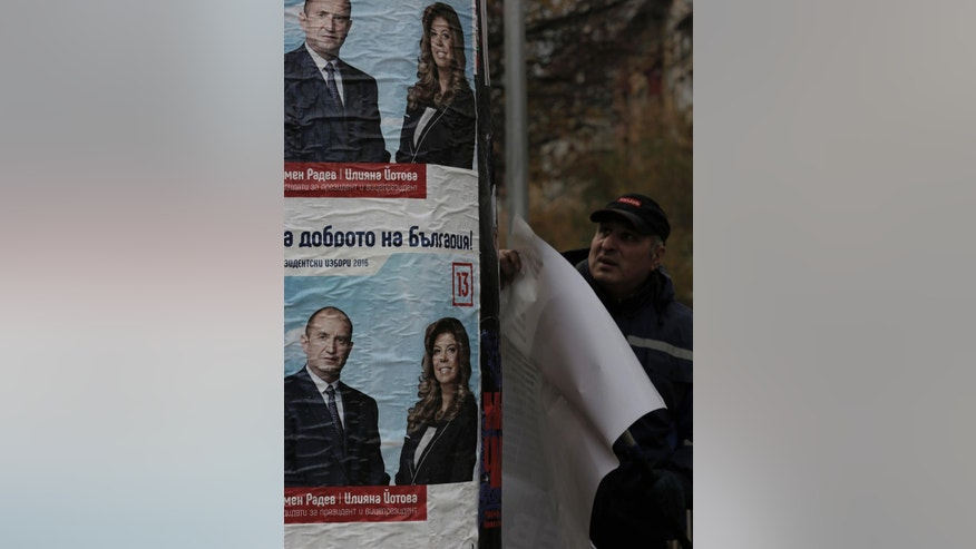 A man sticks up posters of Bulgarian Socialists' Party candidate Rumen Radev, left, ahead of Presidential elections runoff on Sunday, Sofia, Bulgaria, Thursday, Nov. 10, 2016. Bulgarians will go to the polls Sunday to choose their new president in a contested run-off that has become a referendum on the fate of the center-right government of Prime Minister Boiko Borisov. (AP Photo/Valentina Petrova)