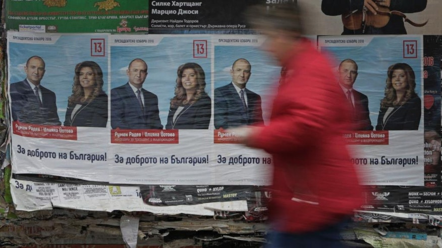 A woman passes in front of posters of Bulgarian Socialists Party candidate Rumen Radev Sofia, Bulgaria, Thursday, Nov. 10, 2016, ahead of the presidential elections runoff on Sunday. Bulgarians will go to the polls Sunday to choose their new president in a contested run-off that has become a referendum on the fate of the center-right government of Prime Minister Boiko Borisov. (AP Photo/Valentina Petrova)