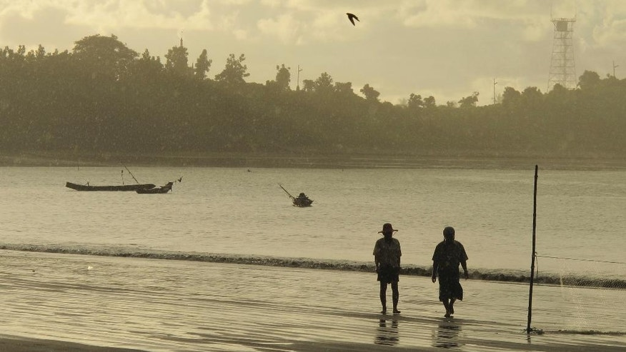 In this Wednesday, Oct. 5, 2016 photo, people walk on a beach in Kyaukpyu on the Bay of Bengal in the Rakhine region, Myanmar, where many residents rely on fishing and farming to survive. China's big development plans for the town on Myanmar's west coast appear to hold few opportunities for local residents. Pipelines, an oil refinery, a deep-water port and other projects may create few jobs for Burmese, who could be forced to give up their land without compensation. Residents' hope for factories that create jobs may never be realized. (AP Photo/Elaine Kurtenbach)