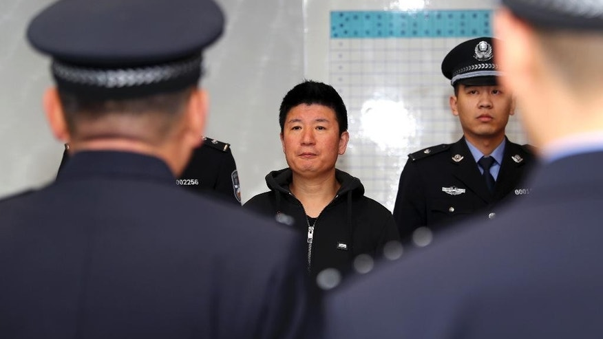 In this photo released by Xinhua News Agency, Yan Yongmin, a graft fugitive who had been on the run for 15 years, arrives at Capital International Airport in Beijing, capital of China, Nov. 12, 2016. The former drug company chairman who was on a list of China's 100 most-wanted fugitives abroad has returned after 15 years on the lam in New Zealand and Australia, the government announced Saturday. (Yin Gang/Xinhua via AP)