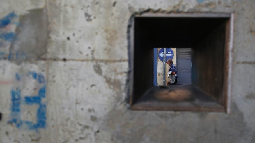 "A man is photographed through a battle hole in a wall near the UN buffer zone, ""Green Line"" that divide the Greek and Turkish Cypriot controlled areas in divided capital Nicosia in this eastern Mediterranean island of Cyprus, Friday, Nov. 11, 2016. The rival leaders of ethnically divided Cyprus are locked in crucial talks in Mont Pelerin, Switzerland that will determine whether a peace deal is within reach. (AP Photo/Petros Karadjias)"