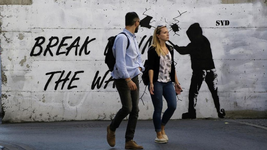 "A couple walk in front of a wall with graffiti, near the UN buffer zone, ""Green Line"" that divide the Greek and Turkish Cypriot controlled areas in divided capital Nicosia in this eastern Mediterranean island of Cyprus, Friday, Nov. 11, 2016. The rival leaders of ethnically divided Cyprus are locked in crucial talks in Mont Pelerin, Switzerland that will determine whether a peace deal is within reach. (AP Photo/Petros Karadjias)"