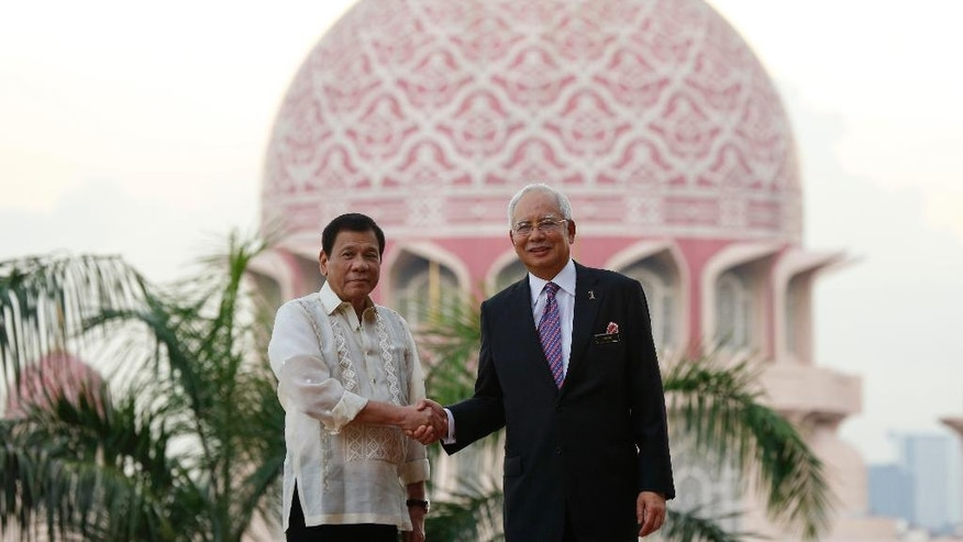Philippines President Rodrigo Duterte, left, and Malaysia's Prime Minister Najib Razak pose for photographs during a welcoming ceremony in Putrajaya, Malaysia, Thursday, Nov. 10, 2016. (AP Photo/Lim Huey Teng)