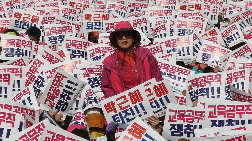 "A South Korean protester stands as her colleagues hold up cards during a rally calling for South Korean President Park Geun-hye to step down in Seoul, South Korea, Saturday, Nov. 12, 2016. Tens, and possibly hundreds, of thousands of South Koreans were expected to rally in Seoul on Saturday demanding the ouster of Park in what would be one of the biggest protests in the country since its democratization about 30 years ago. The signs read ""Park Geun-hye should step down."" (AP Photo/Ahn Young-joon)"