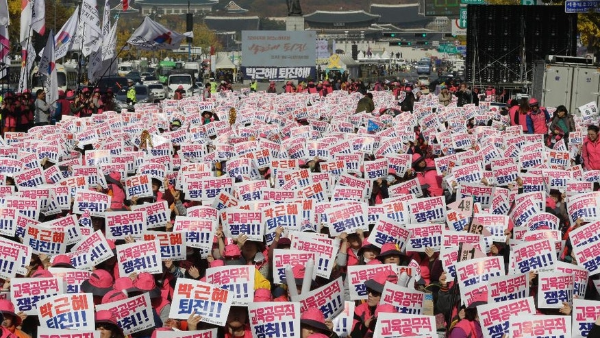 "South Korean protesters hold up cards during a rally calling for South Korean President Park Geun-hye to step down in Seoul, South Korea, Saturday, Nov. 12, 2016. Tens, and possibly hundreds, of thousands of South Koreans were expected to rally in Seoul on Saturday demanding the ouster of Park in what would be one of the biggest protests in the country since its democratization about 30 years ago. The letters read ""Park Geun-hye should step down."" (AP Photo/Ahn Young-joon)"