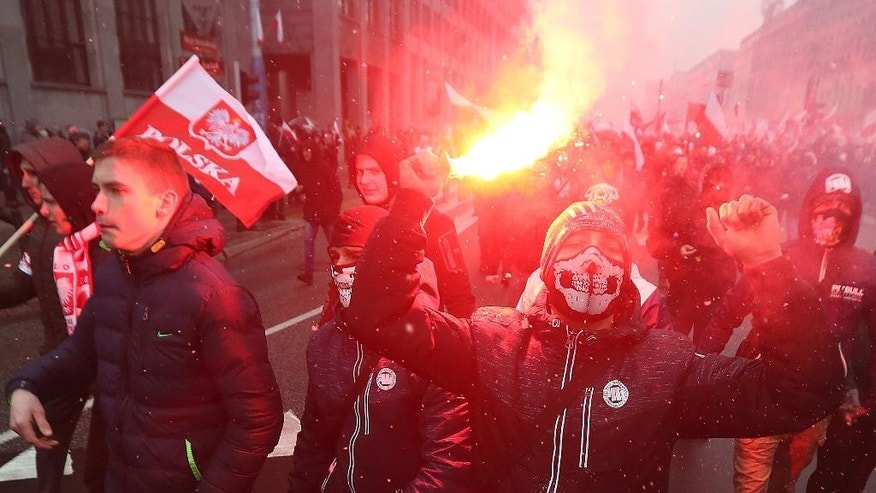 Nationalists, burning flares as they march in large numbers through the streets of Warsaw to mark Poland's Independence Day in Warsaw, Poland, Friday, Nov. 11, 2016.   (AP Photo/Czarek Sokolowski)