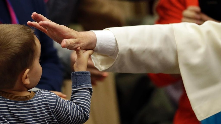 Pope Francis blesses a child during an audience with the participants of homeless jubilee in the Paul VI Hall at the Vatican, Friday, Nov. 11, 2016. (AP Photo/Alessandra Tarantino)