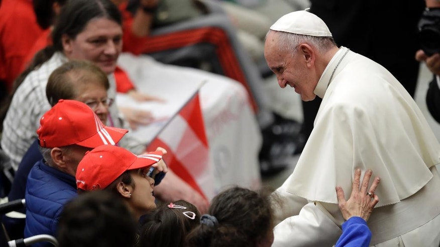 Pope Francis is greeted by faithful during an audience with the participants of homeless jubilee in the Paul VI Hall at the Vatican, Friday, Nov. 11, 2016. (AP Photo/Alessandra Tarantino)