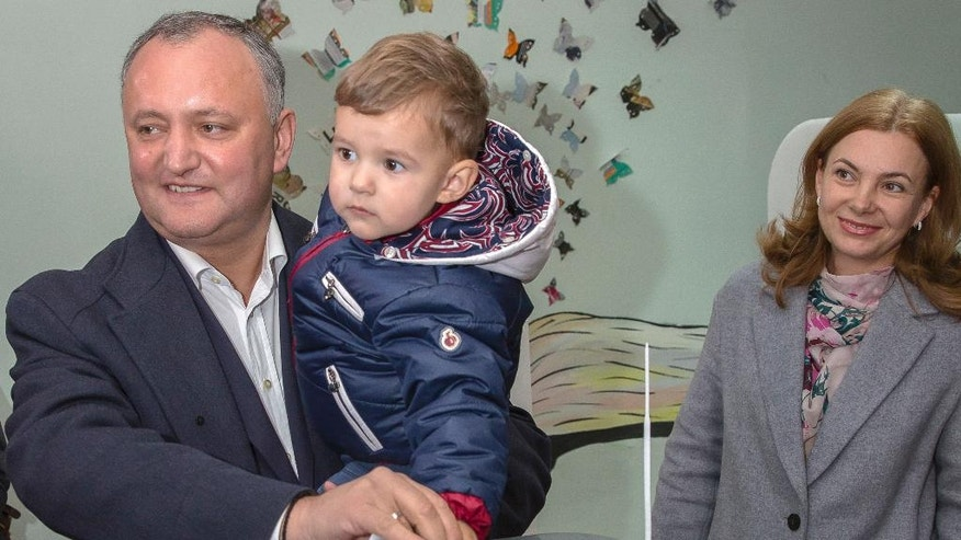 FILE - This is a Sunday, Oct. 30, 2016  file photo of the leader of Socialists Party Igor Dodon as he casts his ballot, holding his son Nikolai while his wife Galina watches, at a polling station during the presidential elections in Chisinau, Moldova. Moldovans will directly elect their president on Sunday Nov. 13, 2016 for the first time in 20 years. The favorite is Socialist Igor Dodon who wants the ex-Soviet republic to return to the Russian orbit. Rival Maia Sandu believes the agricultural nation of 3.5 million, bordering Ukraine and European Union member Romania, would secure a more prosperous future in Europe. (AP Photo/Roveliu Buga, File)