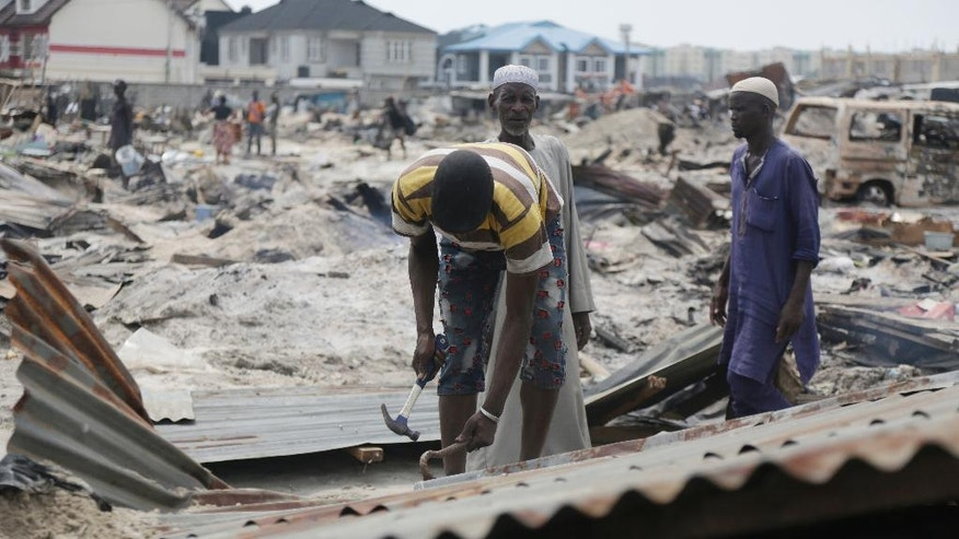 Residents salvage roofing sheets from demolished houses that were set ablaze by government officials in Lekki, Lagos, Nigeria. Saturday, Nov. 12, 2016, Amnesty International says as many as 30,000 people in Nigeria's commercial capital are homeless after their community was set ablaze and demolished this week. (AP Photo/Sunday Alamba)